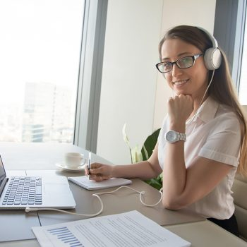 Woman sitting in front of laptop with headphone on head and writing in notebook. Female increases foreign language vocabulary with online courses. Entrepreneur communicates with colleagues in Internet
