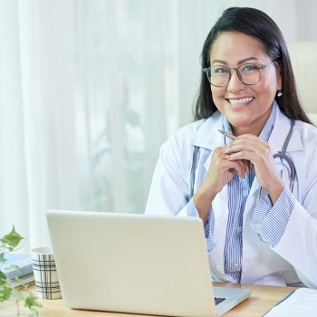 Beautiful adult Thai woman in doctor coat and glasses sitting at table with laptop smiling at camera